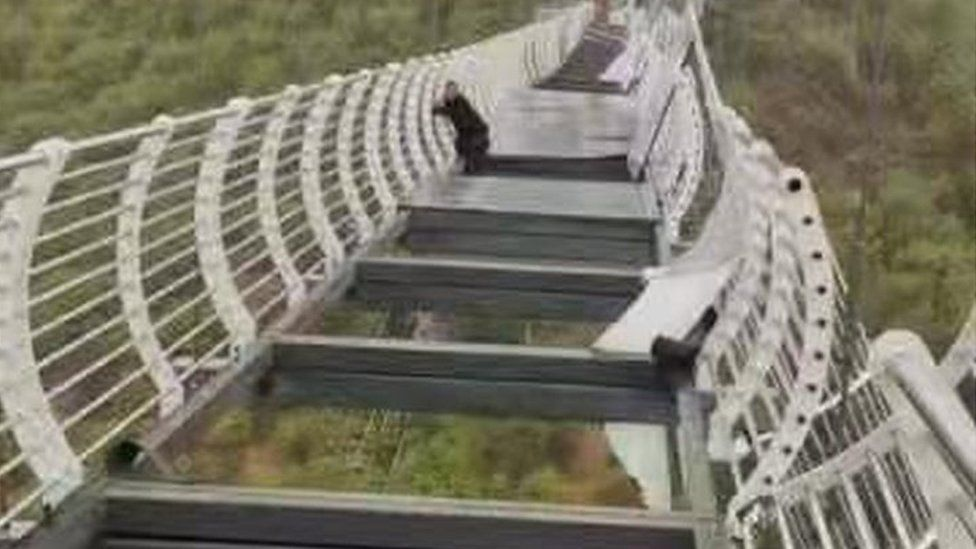 Chinese man trapped on 100m-high glass bridge shattered by wind in China 62